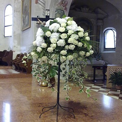 una porta fiori con delle rose bianche