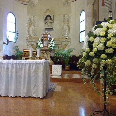 una porta fiori con delle rose bianche in una chiesa
