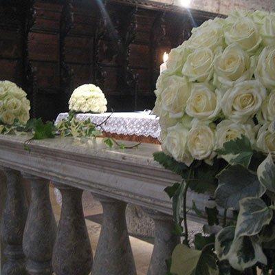 dei bouquet di rose bianche in una chiesa