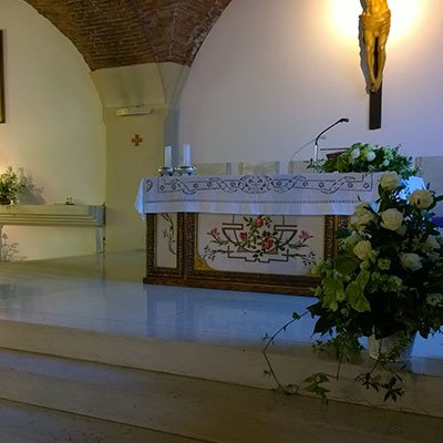 un vaso di fiori bianchi e dell'edera in una chiesa