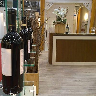 delle bottiglie di vino su un banco e accanto un vaso di fiori