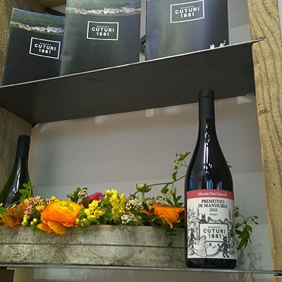 due bottiglie di vino e accanto un cestino di fiori arancioni