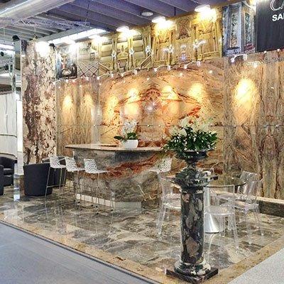 dei tavoli in marmo con due vasi di fiori sopra e delle sedie trasparenti