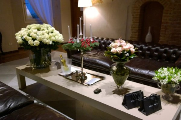 un tavolino con dei vasi di fiori e un candelabro