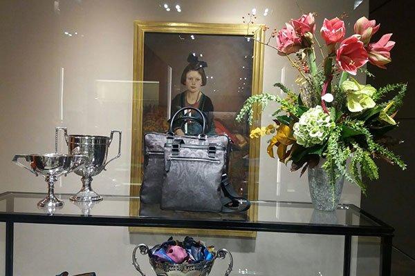 un tavolino con due borse e accanto un vaso in vetro con dei fiori grandi di color rosso