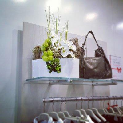una mensola di vetro con una borsa e un vaso di fiori