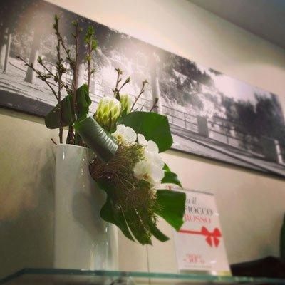un vaso alto con dei fiori bianchi