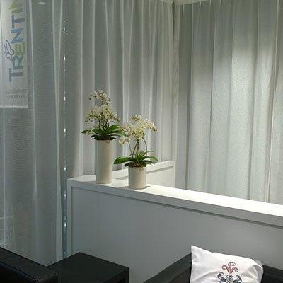 due vasi bianchi a forma di cilindro con dei fiori