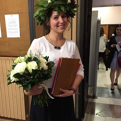 una ragazza con una ghirlanda delle foglie in testa e un vaso di fiori bianchi
