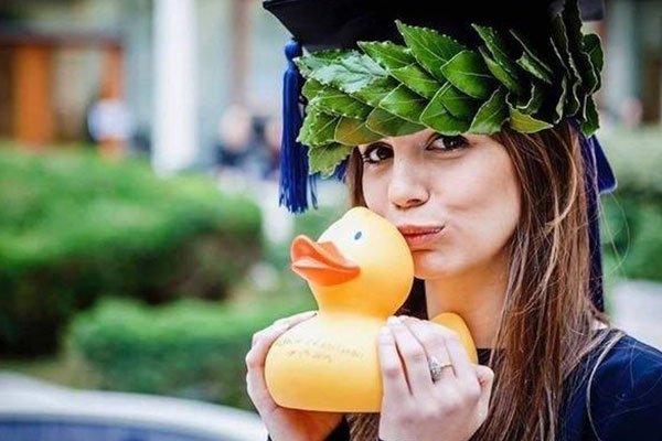 una ragazza con una ghirlanda di foglie in testa e una paperella in mano