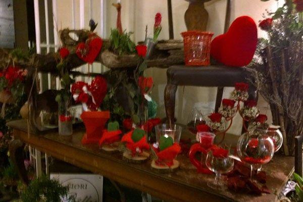 una mensola con dei vasi in cristallo e altri oggetti di color rosso