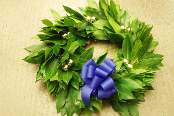 una ghirlanda delle foglie con campanelle e un fiocco azzurro