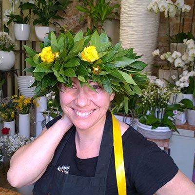 una donna con una ghirlanda delle foglie e delle rose di color giallo