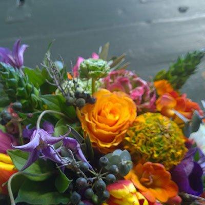 una composizione dei fiori di color arancione, viola e verde