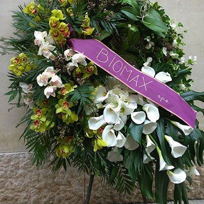 una composizione di fiori bianchi e di altri colori e un nastro viola con scritto Biomax