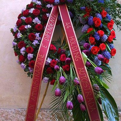 una corona di rose rosse,azzurre e viola con un nastro bordeaux con delle scritte