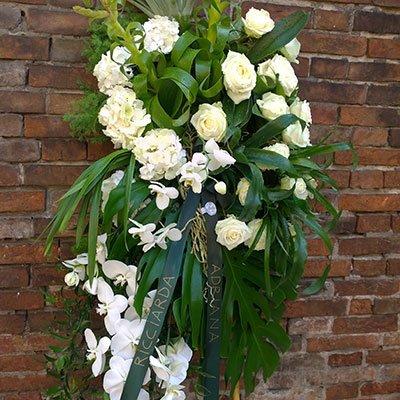 una corona di rose bianche e un nastro verde con scritto Riccarda, Adriana