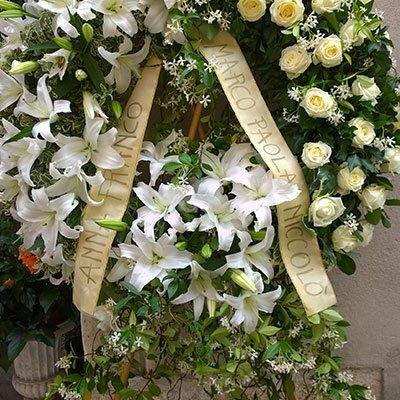 una corona di fiori con un nastro con scritto Anna Franco Marco Paola Niccolo'