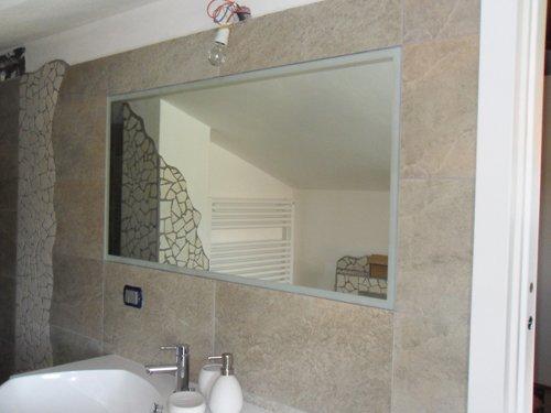 specchio in un bagno con lavabo e porta sapone