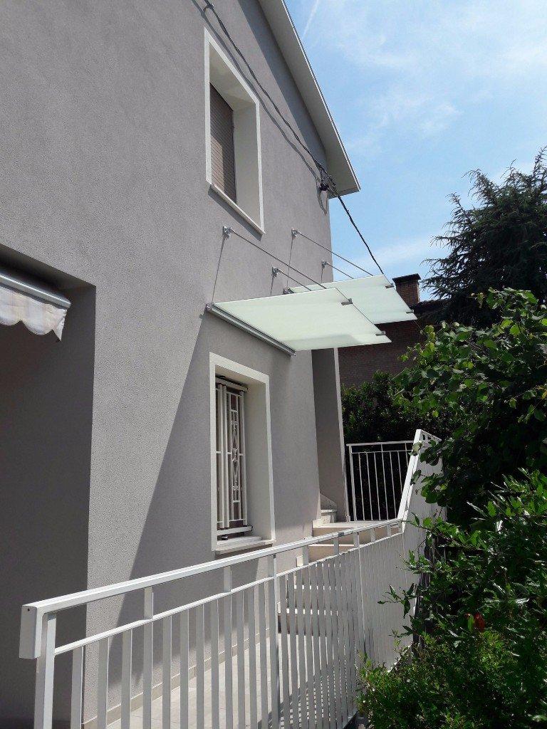 doppia pensilina sopra una finestra e delle scale in balcone