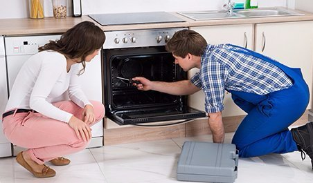 Professional repairing electronic equipment in a kitchen