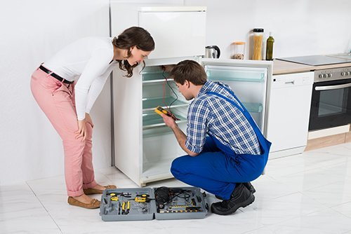 Professional servicing a fridge in kitchen