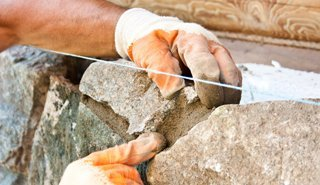 A workman fixing the grout on a stone wall