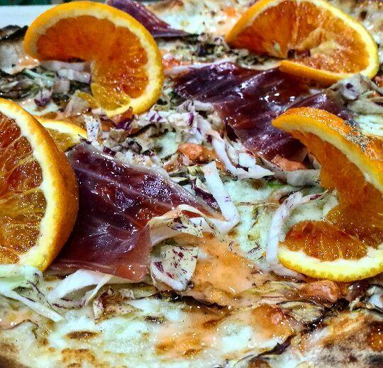 una pizza con bresaola verdure e arancia