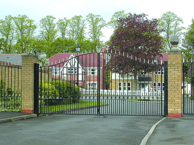 Iron gate with gold spiked tips leading to a private housing estate