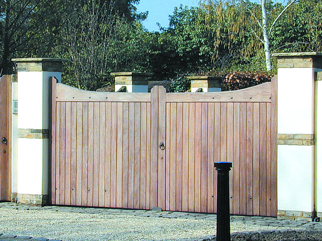 Solid wooden driveway gate with a metal knocker