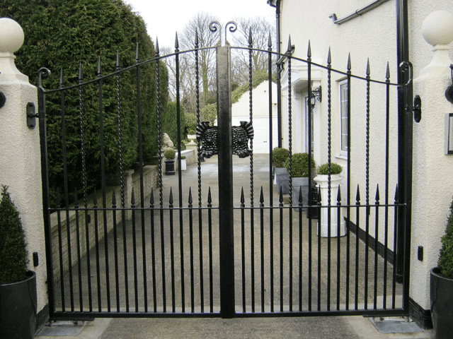 Black iron gates beside a white house, leading to a private driveway