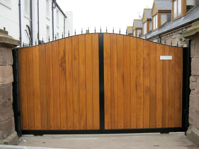 Varnished hardwood gates with a painted black metal frame