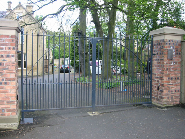 Grey painted metal swing gates leading to large stately home.