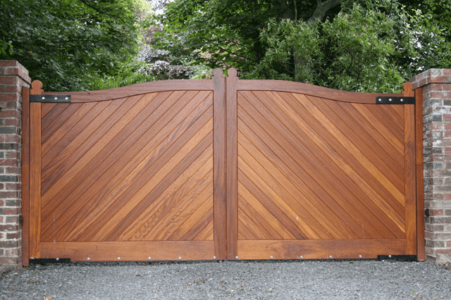 Hardwood gates leading to a private driveway lined with trees
