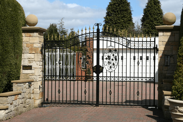Wrought iron gates with floral patterns leading to the driveway of a private home