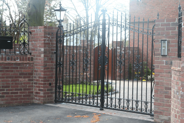 Metal driveway gates with a curved pattern leading to a private home