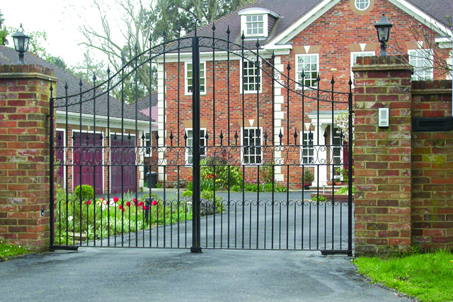 Wrought iron swing gates outside a large home with 3 garages