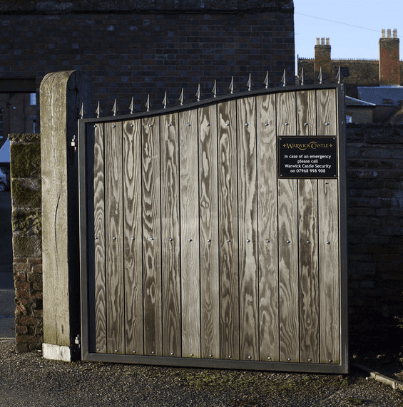 Wooden gates with a sign for Warwick Castle