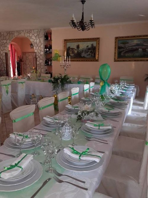 una tavolata apparecchiata con dei tovaglioli con dei fiocchi verdi