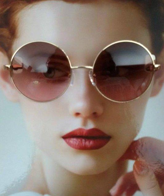 una ragazza con degli occhiali da sole rotondi