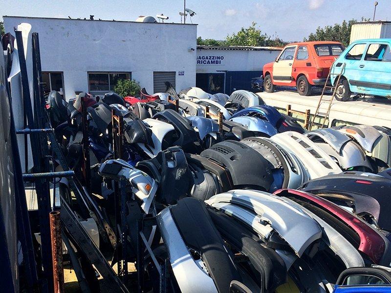 fila di parti auto usate davanti di magazzino
