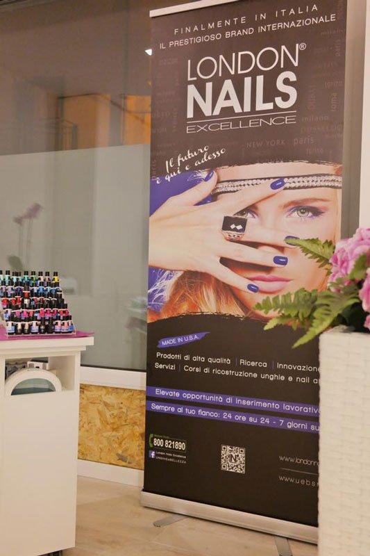un cartellone di london nails excellence e sulla destra un mobile bianco dei smalti