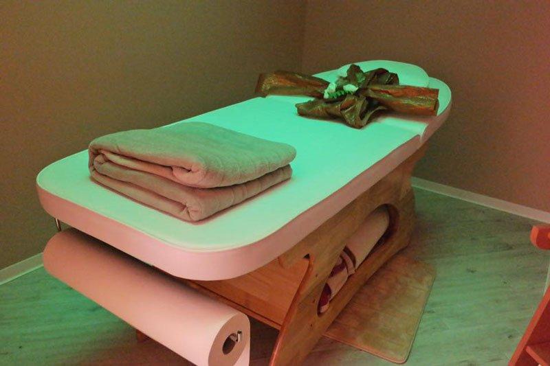 Una stanza con un lettino con di legno con sopra dei asciugamani piegati