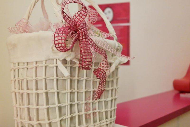 Un cestino bianco con fiocchi di color bianco e rosso