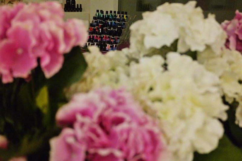 Uno stand con dei smalti di varie colori e fiori di color bianco e rosa