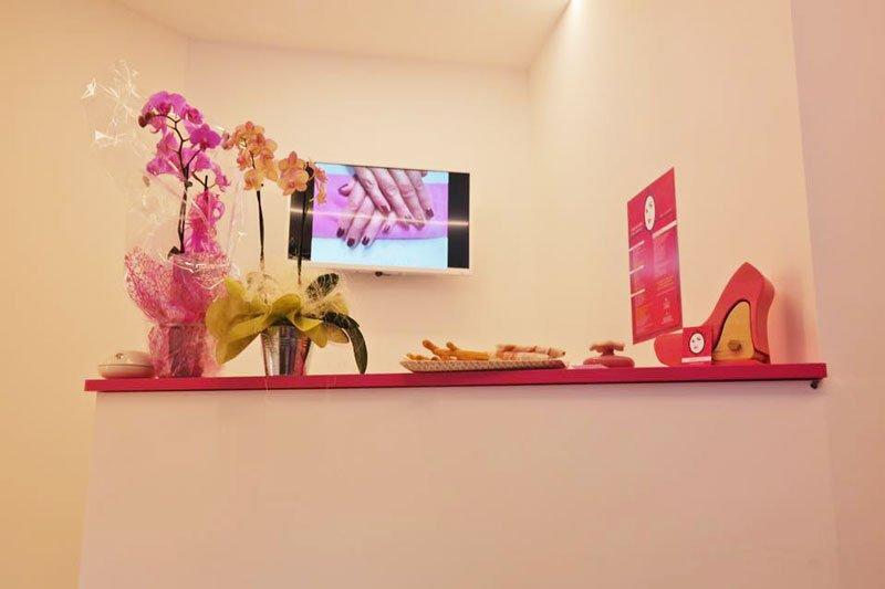 Una mensola rosa con degli oggetti, vasi di orchidee e tv a muro