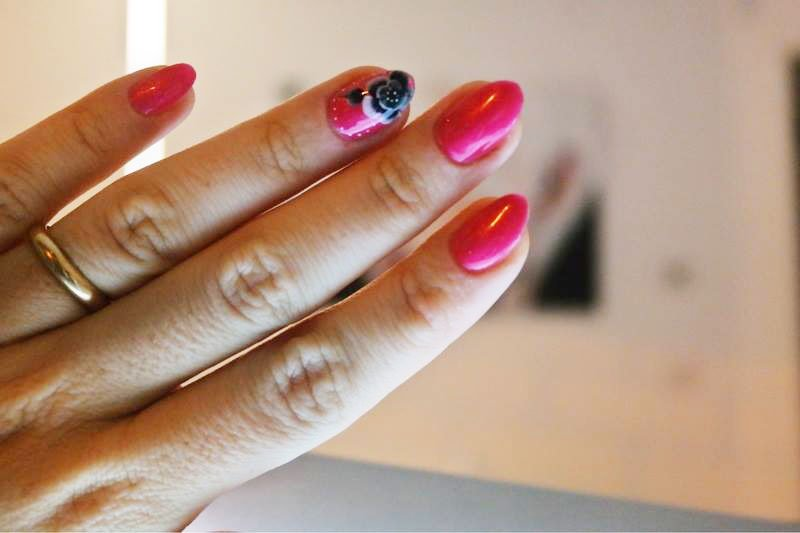 Una mano di una donna con uno smalto rosa e disegni di fiori