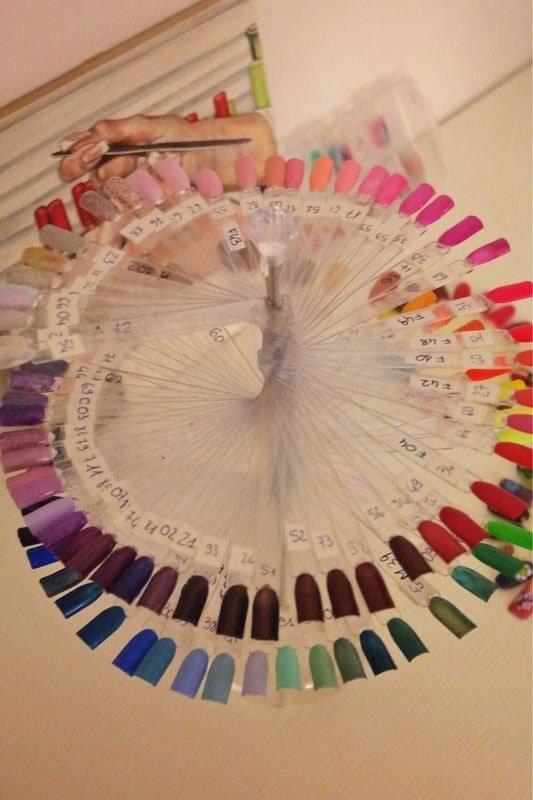 Una palette di unghie artificiali con smalti di varie colori