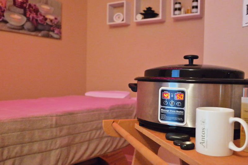 Una stanza con lettino e sulla destra una fornetto per scaldare cera e una tazza con scritto Antos