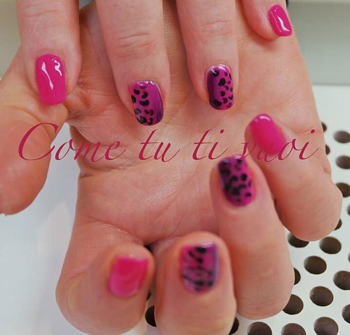 Mani di una donna con le unghie di color viola e rosa e scritta Come Tu Ti Vuoi